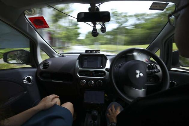 新加坡,一名驾驶员正在测试NuTonomy的一辆自驾驶汽车。这家公司在新加坡运营自驾驶出租车,最近开始在波士顿提供这项服务。